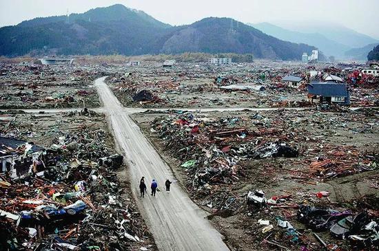 因为几乎没有任何预警,致命的日本东北大地震和海啸摧毁了日本的陆前高田市。灾难过后,居民走在废墟中。