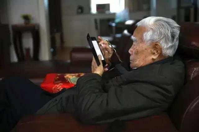 97岁的张世英依然思维活跃、与时俱进。图为他在智能手机上浏览文章。赵凤兰摄.jpeg