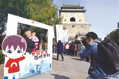 10月15日上午,北京市东城区第七次全国人口普查宣传日活动在钟鼓楼广场举行。图为居民在活动现场参与互动拍照体验。 图片来源:人民视觉