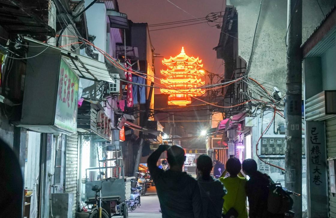"""市民在武汉市武昌区著名的老街得胜路桥拍照(3月28日摄)。自2020年4月8日武汉""""解封"""",至今一年过去了,夜幕下的武汉,各个角落都焕发着活力,人们逛街吃饭休闲,感受城市夜生活的魅力。新华社 图"""